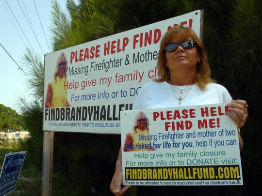 In a 2007 photo, Lynn Troup of West Melbourne poses at the intersection of Babcock Street and Malabar Road in Palm Bay near an advertisement for help finding her friend, Brandy Hall. This year marks the 10th anniversary of Hall's disappearance in August 2006.