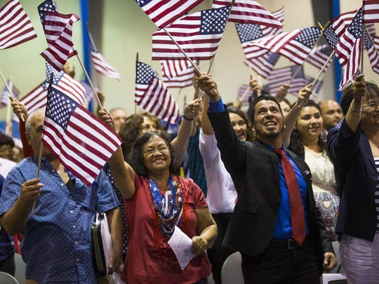 Candidates wave flags after taking an oath of allegiance during a naturalization ceremony at South Mountain Community College in Phoenix, Arizona on Tuesday, July 4, 2017. 151 people from 43 countries were sworn in as citizens.