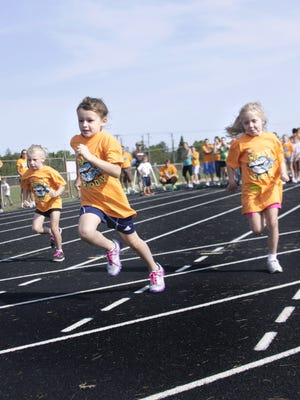 Children run in a 100 meter dash on the Apollo High School track during the Family Track & Field Day in 2012.