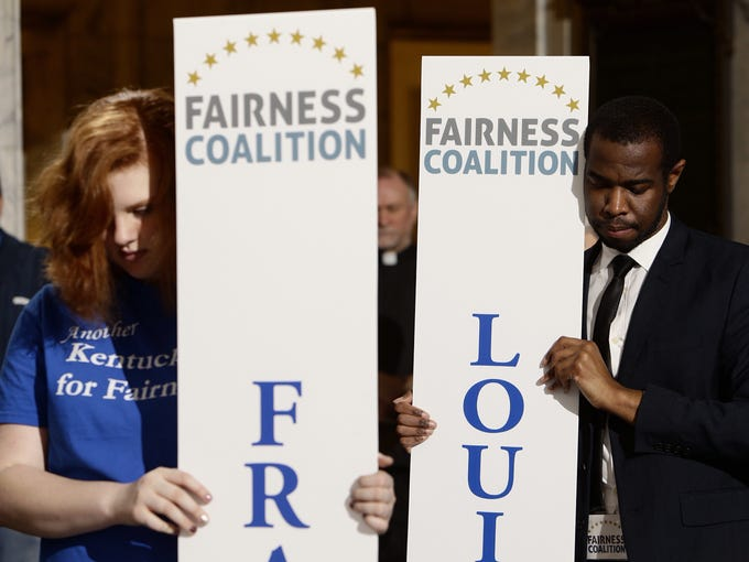 Grace Mitchell of Frankfort, left, and Keith Brooks Fairness Campaign Co-Coordinator bow their heads during a prayer following the fairness rally, Wednesday, Feb. 19, 2014 in the Capitol Rotunda at the Capitol in Frankfort.   By Jonathan Palmer/Special to the Courier-Journal