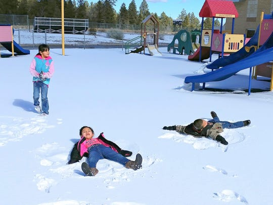 Two students in Kaverly Smith's first grade class at the Mescalero School do their best to convince their teacher they are angels, at least in the snow.