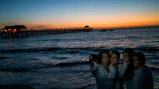 Adriana Silva, Marlene Munoz, Jennifer Munoz, and Monica Garcia take a picture together with the sunset before the fireworks during the New Year's Eve celebration at Naples Pier on Dec. 31, 2016, in Naples.