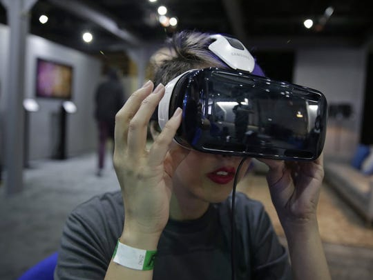 A woman demonstrates the Oculus virtual reality headset