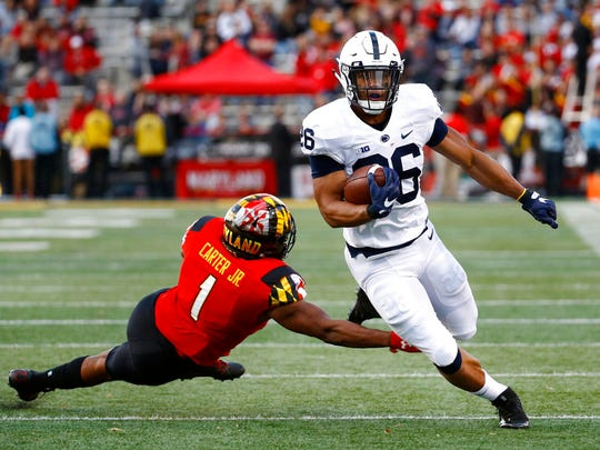 Penn State running back Saquon Barkley, right, rushes past Maryland linebacker Jermaine Carter Jr. in the first half of an NCAA college football game in College Park, Md., Saturday, Nov. 25, 2017.