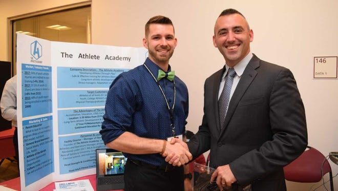 The Athlete Academy owner Cory Revel is congratulated by Salisbury Mayor Jake Day after winning the Mayor's Prize in Salisbury University's entrepreneurship competition.