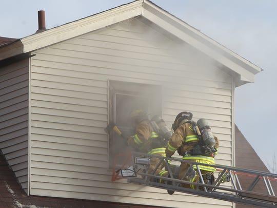 A Cheviot firefighter uses an ax to break through a