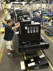 Workers at Generac Power Systems assemble a generator onto an engine Thursday, Aug. 10, 2017, at the Oshkosh plant, which makes 150-kilowatt to 2-megawatt diesel and natural gas generators.