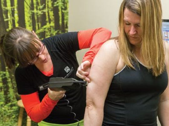 Trainer Chelsea Hart measures Jennifer Doyle Vancil's bodyfat percentage during her general fitness assessment at Miramont Central.