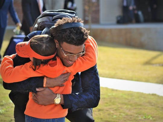 Clemson quarterback Kelly Bryant hugs Savana Jones, 8, for good luck before boarding a bus and heading for New Orleans with the rest of the Clemson Football team on Dec. 27, 2017.