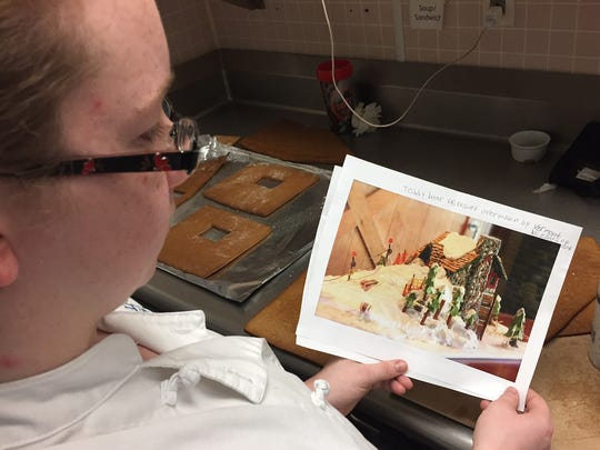 Bree Messier, a senior at Delaware Technical and Community College, looks at a picture of what her gingerbread house will like while the sections of her house cool off.