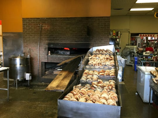 A full rack of bagels in reserve sits besides the still-glowing wood fire oven Saturday morning, Nov. 4, 2017, at Myer's Bagel Bakery on Pine Street in Burlington.