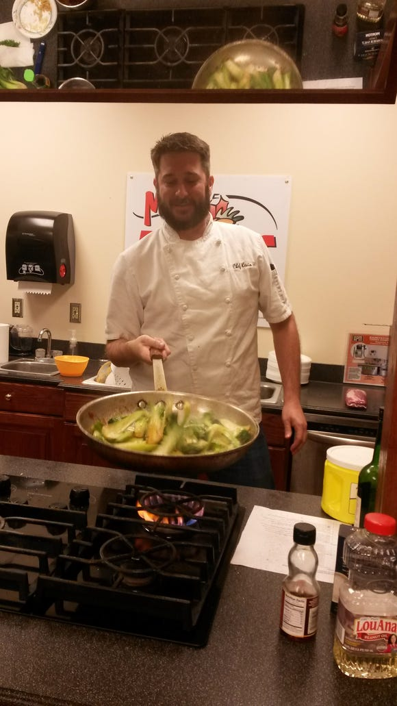 Chef Kevin Hawkins makes stir fried bok choy at one of Rouses cooking classes.