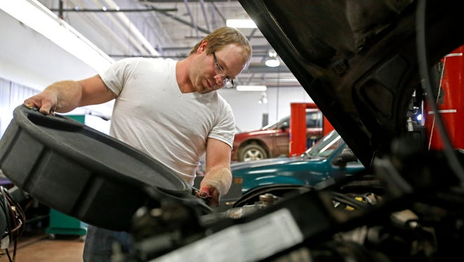 Buck Brown, 31, of Flora Vista, works on a vehicle on Tuesday during class in the automotive garage at the San Juan College School of Trades and Technology building in Farmington.