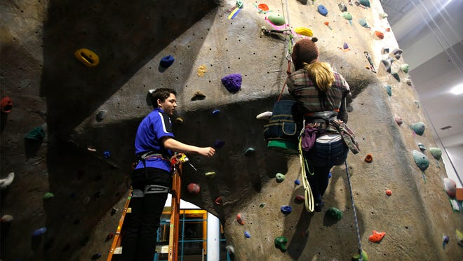 Zach Quintero and Eliza Elsbury work on the climbing wall on Thursday at San Juan College's Health and Human Performance Center in Farmington.