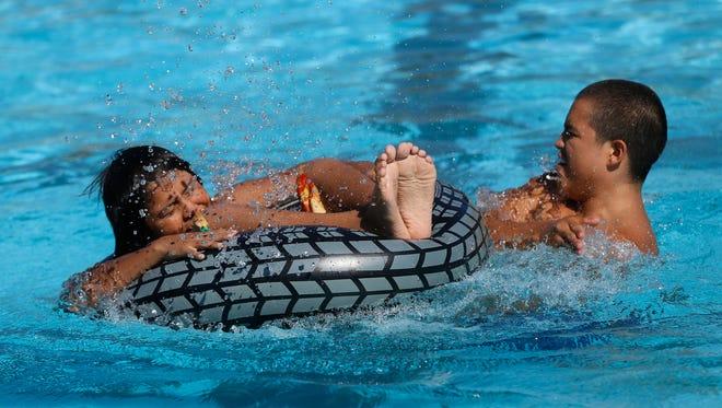 Keeyian Hungary, left, and Raheem Benally splash in the Brookside Pool on Aug. 29, 2015n.