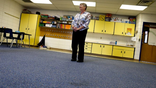 Luanne Davis, principal at Bluffview Elementary School, points out what she suspects is possible mold on her carpet on Aug. 24 at the school in Farmington.