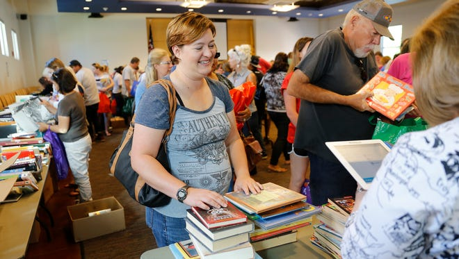 Tami Jo Bechdol makes her purchases during last year's book sale at the Farmington Public Library.