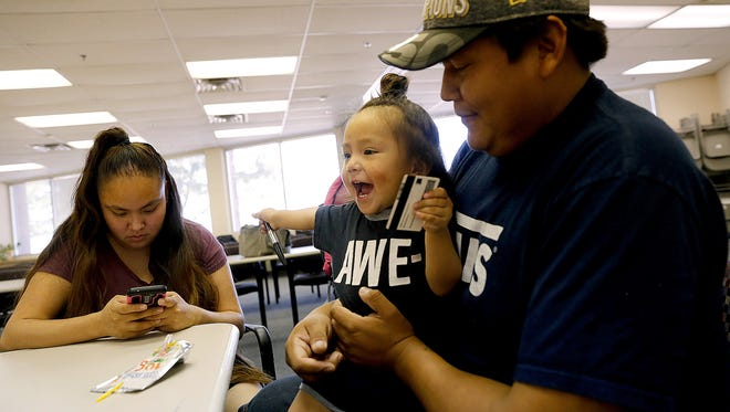 Shenika Sam, left, and Myron Ben fill out paperwork for a birth certificate for their son Mikaiya Ben in a file photo from Sept. 22, 2016, at the Northern Navajo Agency Nataani Nez Complex in Shiprock.