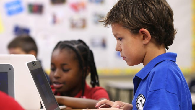 Fourth-graders Oliver Wilkinson, 9, and Jada Wright (background) work on computers during a technology culture class at Irvington Community Elementary School, 6705 Julian Ave., Indianapolis. The school is a tuition-free public charter school sponsored by the Indianapolis Mayor's Office of Education Innovation.