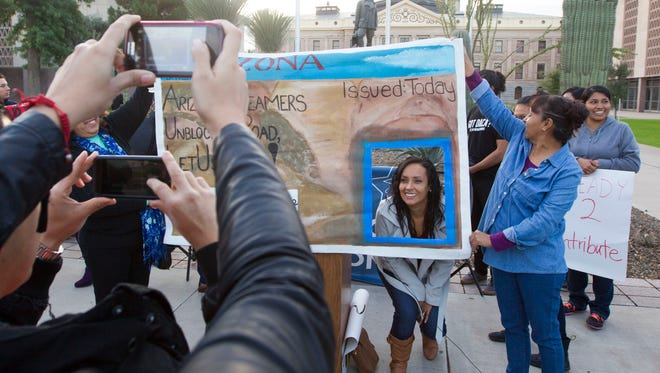"Erika Andiola gets her picture taken with a giant license display while celebrating at state Capitol in Phoenix Wednesday, Dec. 17, 2014, after the 9th U.S. Circuit Court of Appeals instructed U.S. District Court Judge David Campbell to issue a preliminary injunction blocking Gov. Jan Brewer from denying driver's licenses to young Arizona immigrants known as ""dreamers."""