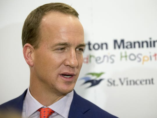 Peyton Manning talks with media before the evening's