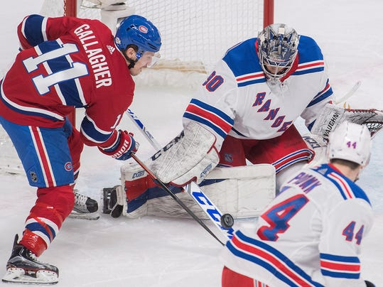 Montreal Canadiens' Brendan Gallagher (11) moves in on New York Rangers goaltender Alexandar Georgiev as Rangers' Neal Pionk defends during the first period of an NHL hockey game Thursday, Feb. 22, 2018, in Montreal. (Graham Hughes/The Canadian Press via AP)