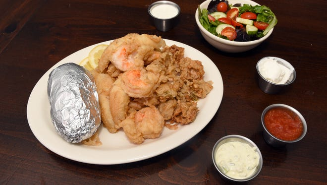 The seafood platter at Jake's in McConnelsville is shown with deep fried jumbo shrimp, Lake Erie yellow perch and oysters. Customers have a choice of crab cake, scallops, clam strips or the aforementioned seafood all made with Jake Woodward's homemade breading.