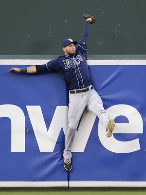 FILE - In this Monday, Aug. 31, 2015 file photo,Tampa Bay Rays center fielder Kevin Kiermaier collides with the outfield wall after catching a fly ball by Baltimore Orioles' Manny Machado in the first inning of a baseball game in Baltimore. Everyone has seen an outfielder receive a tip of the cap or a jubilant fist bump from a pitcher after a home run robbery. This is a story about what happens after they leave the field. (AP Photo/Patrick Semansky, File)