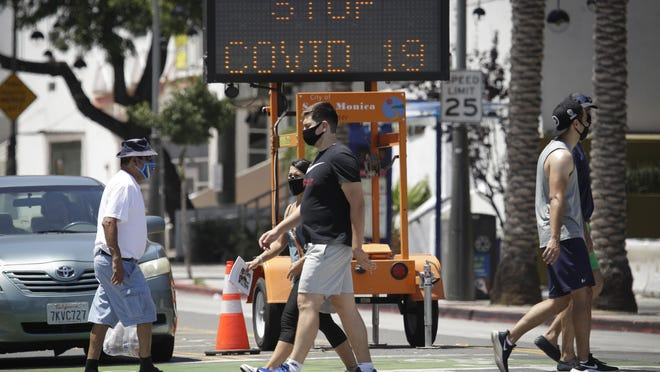 Pedestrians wear masks as they cross a street amid the coronavirus pandemic Sunday, July 12, 2020, in Santa Monica, Calif. A heat wave has brought crowds to California's beaches as the state grappled with a spike in coronavirus infections and hospitalizations.