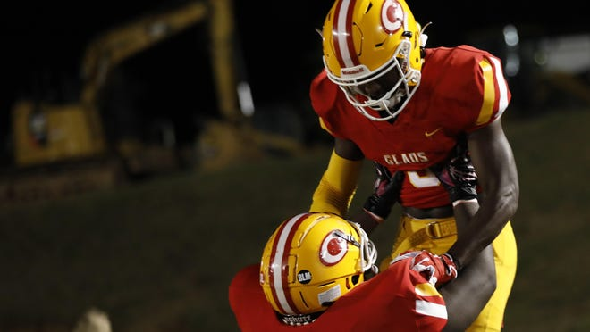 Clarke Central's Nono Mack (3) celebrates with Clarke Central's Yoshi Diekumpuna  (76) after scoring a touchdown during the Gladiators' 38-10 win over Jackson County.