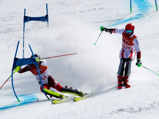 Switzerland's Daniel Yule, left, races Austria's Marco Schwarz in the gold medal race in the alpine team event at the 2018 Winter Olympics in Pyeongchang, South Korea, Saturday, Feb. 24, 2018. (AP Photo/Christophe Ena)
