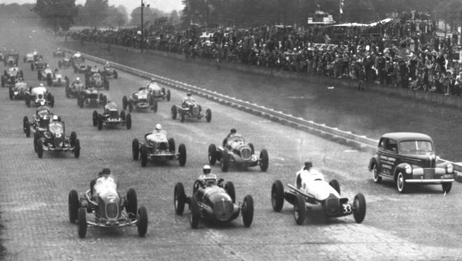 The start of the 1940 Indianapolis 500 with the pace car pulling off to the side.  Mauri Rose, Wilbur Shaw and Rex Mays (left to right) led the pack to the first turn.