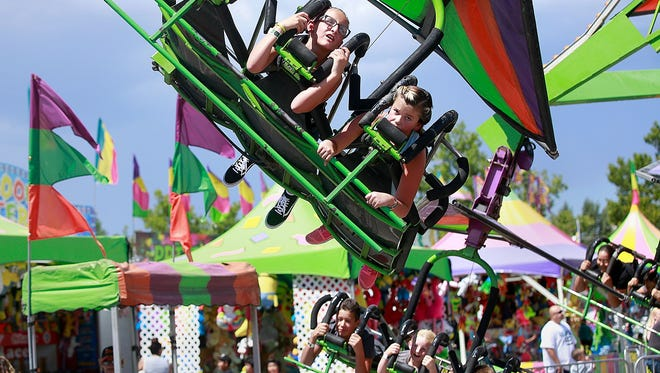 Daydre Silva, 10, left, and Pixie Littlefield, 10, of Aztec, ride the Cliff Hanger during the San Juan County Fair on Aug. 13 at McGee Park.