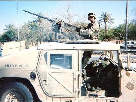 Shaun Dickmyer mans a gun atop a Humvee during his