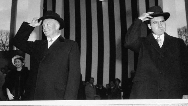 President Dwith Eisenhower and Vice President Richard Nixon lean toward one another on reviewing stand, and then separate to doff their black homburgs to hold them across their chests in salute of unit passing during the inaugural parade in Washington on Jan. 21, 1957.  (AP Photo)