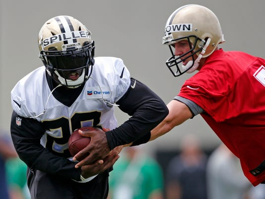 New Orleans Saints quarterback Luke McCown (7) hands off to running back C.J. Spiller (28) during the NFL football team's minicamp in Metairie, La., Tuesday, June 14, 2016. (AP Photo/Gerald Herbert)