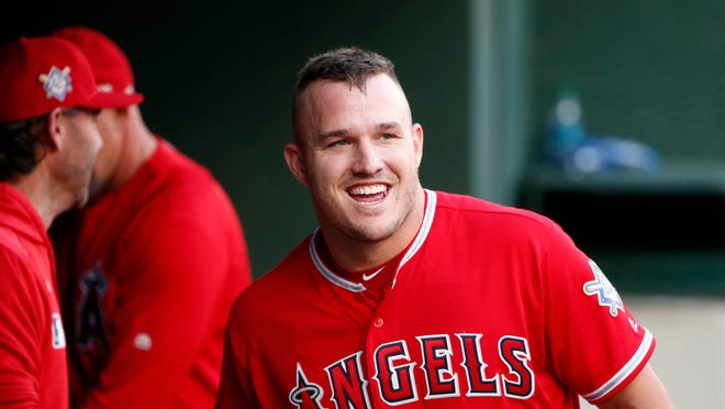 "FILE - In this April 15, 2019, file photo, Los Angeles Angels designated hitter Mike Trout smiles in the dugout after he scored on a home run by Brian Goodwin against the Texas Rangers during the first inning of a baseball game in Arlington, Texas. If Major League Baseball and the players' union can partially save its 2020 season, the potential 60-to 70-game season would be much shorter than the usual 162-game grind. It would look much more like a college baseball season. ""If there's 60 games on the schedule, someone like Mike Trout is going to play 60 games,†former major league baseball player and college coach Tracy Woodson said."