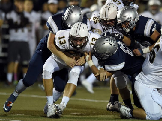 Central quarterback Brennon Harper is sacked by Jackson Ashby (35) and Jarrett Naas (61) of Reitz during the second quarter of sectional semifinal game at the Reitz Bowl in Evansville Friday.