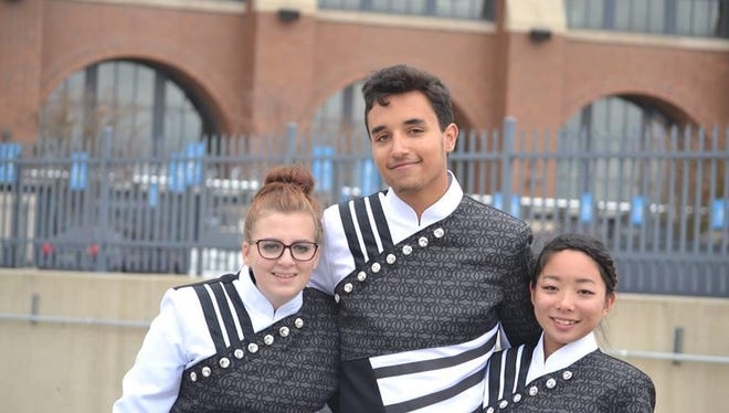 Ryle High School Marching Band drum majors Ella Rowen, Nick Hyett and Manami Horiuchi pose in front of Lucas Oil Stadium in Indianapolis preparing for the Bands of America Grand National Championships.