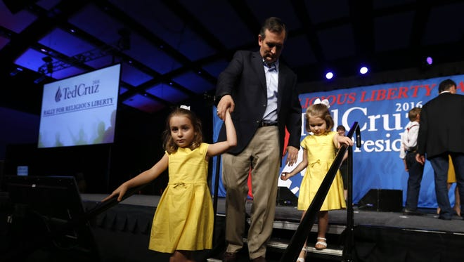 Republican Ted Cruz escorts daughters Caroline, 7 (left), and Catherine, 4, off stage Friday, Aug. 21, 2015, at the Rally for Religious Liberty in Des Moines.