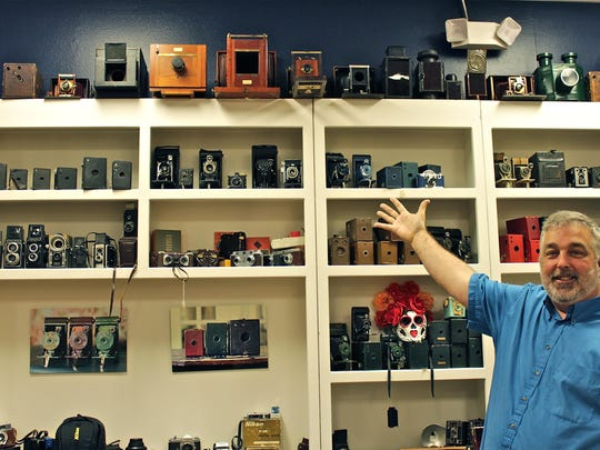 Rob Kepko, store manager for Calagaz Photo, poses in front of his collection of cameras inside Calagaz's shop on North Ninth Avenue.