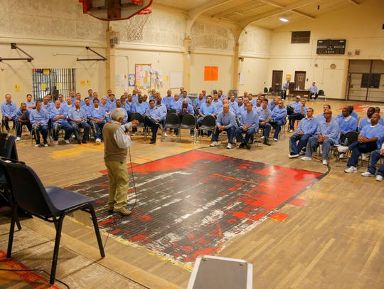 Speaking before a roomful of prison inmates, John Piña