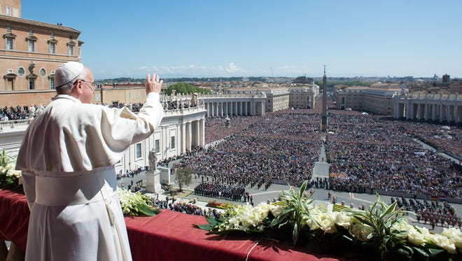 Pope Francis waves to the crowd from the balcony of St. Peter's Basilica, where he delivered the Urbi et Orbi at the end of the Easter Mass in St. Peter's Square at the Vatican on April 20.