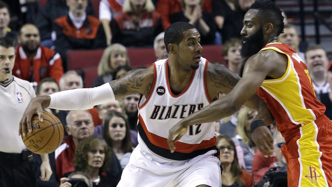 Portland Trail Blazers forward LaMarcus Aldridge, left, works the ball in against Houston Rockets guard James Harden during the first half of an NBA basketball game in Portland, Ore., Wednesday, March 11, 2015.