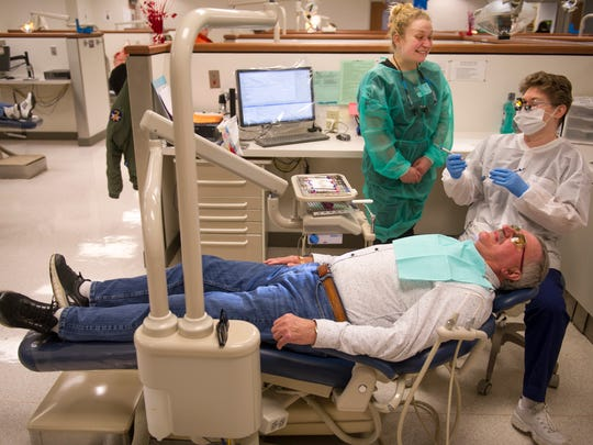Kathy Seib, a dental hygiene instructor at the University of Southern Indiana for 33 years, right, checks on the teeth cleaning work of student Sami Harpenau, top, at the USI Dental Hygiene Clinic Wednesday morning. Jerry Schapker, a U.S. Air Force veteran, had his teeth cleaned by the USI senior.