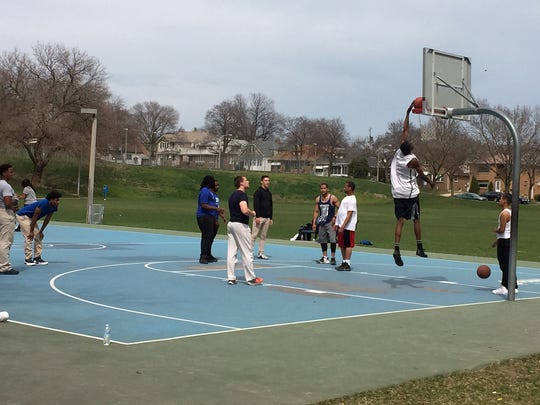 Students and staff from the Academy of Excellence High School in Milwaukee practice basketball skills on the courts at Pulaski Park. The courts and a nearby playground will be relocated within the park when the Kinnickinnic River channel through the park is widened this year.