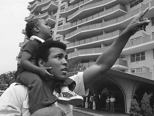 Muhammad Ali carries his son, Muhammad Ali Jr., on