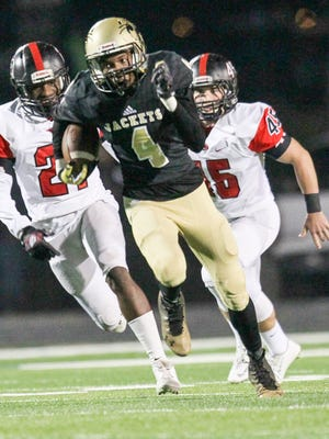T.L. Hanna's A.J. Bryant runs by Hillcrest's Jaiquan Lewis(21), left, and Hillcrest's Garrett Sayegh (45), right, during the first quarter on Friday at T.L. Hanna High School in Anderson.