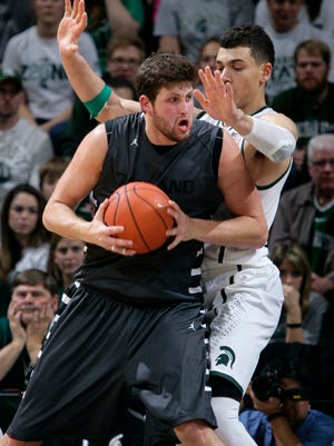 Oakland's Corey Petros, left, maneuvers against Michigan State's Gavin Schilling during the second half of an NCAA college basketball game, Sunday, Dec. 14, 2014, in East Lansing, Mich. Michigan State won 87-61.