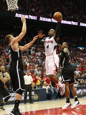 Atlanta Hawks forward Paul Millsap (4) shoots over Brooklyn Nets center Brook Lopez (11) in Wednesday's game.
